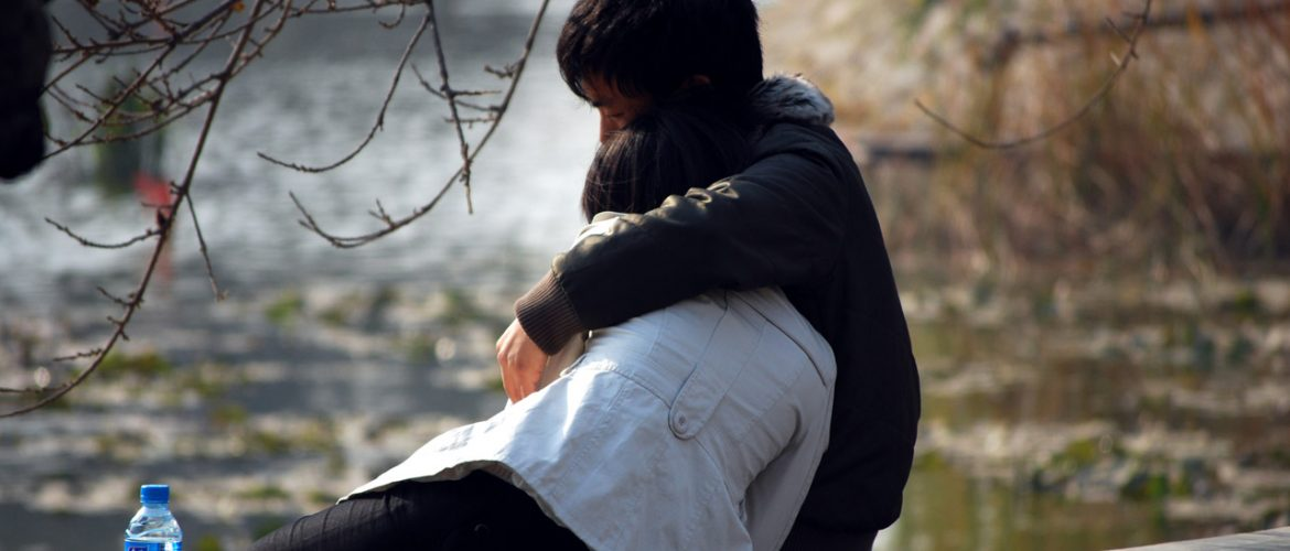 young couple sitting on the ground by water and hugging